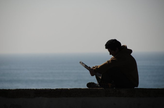 9748-silhouette-of-a-man-reading-by-the-ocean-pv