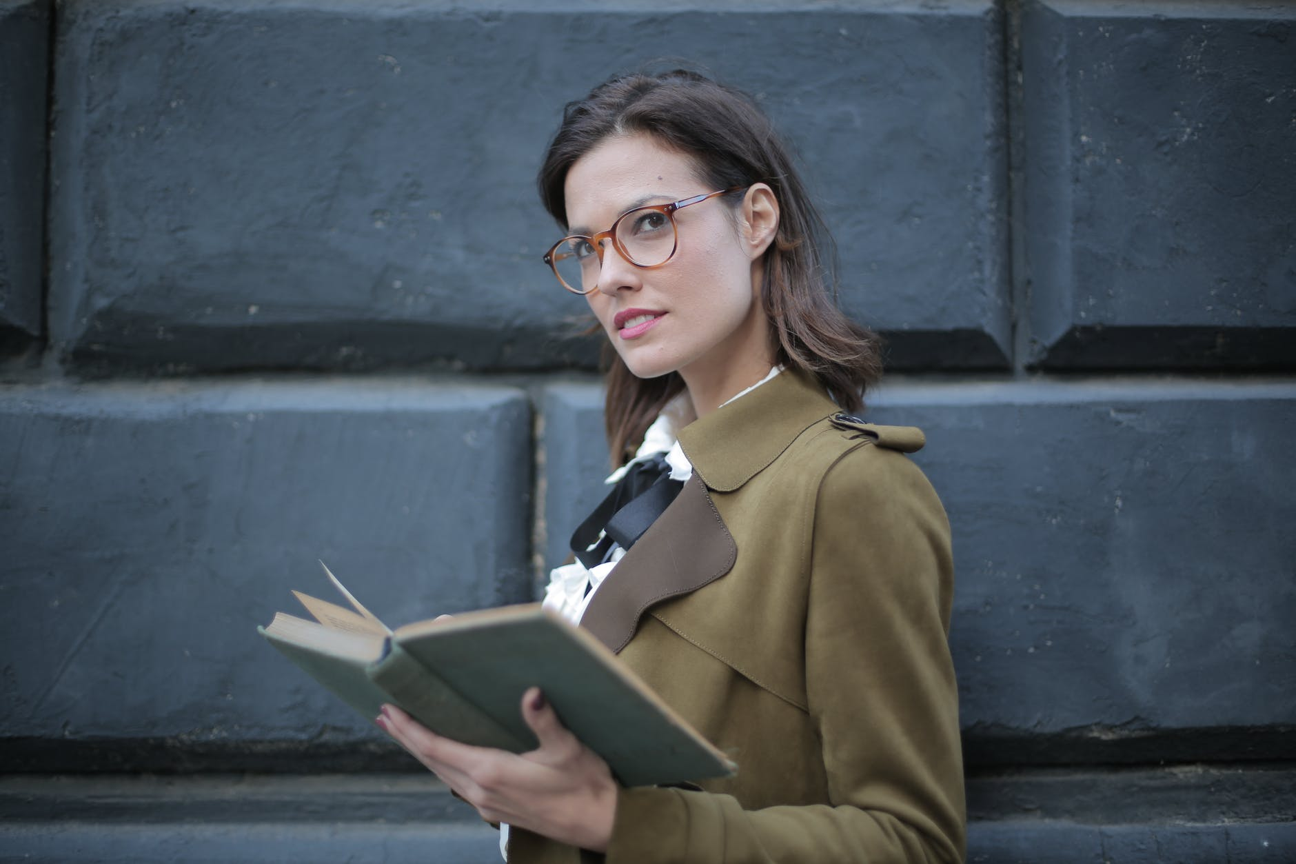 serious adult woman with open book on street against facade of old building in university